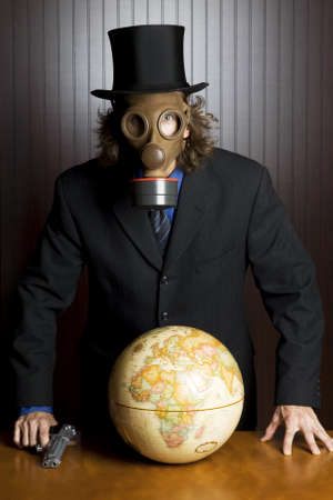 Businessman wearing a gas mask holding a gun to an earth globe