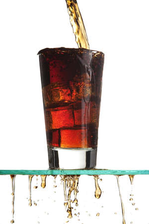 Pouring a soft drink, the liquid overflowing and spilling onto the table, on white.   photo