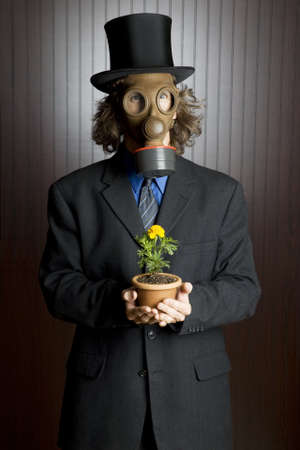Businessman wearing a gasmask holding a flower  photo