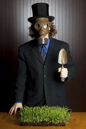gasmask: Businessman wearing a gasmask holding a potting shovel and a flower standing over a patch of grass