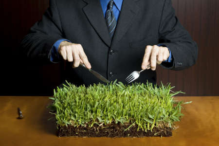 unrelated: Businessman holding a fork and knife cutting into a plate of grass