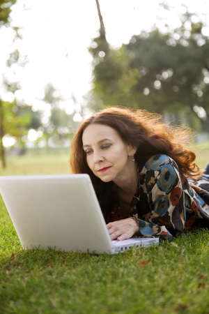 Woman, wearing a hearing aid, working on her laptop in a park. photo