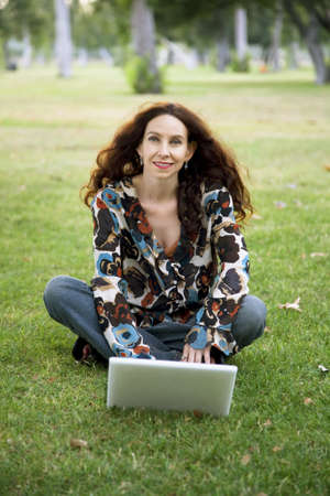 a year older: Woman, wearing a hearing aid, working on her laptop in a park.