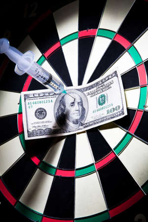 syringes and money stuck on a dartboard  photo