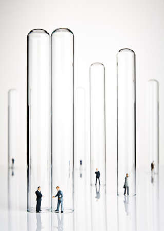 Business figurines placed in and around test tubes Stock Photo - 11132790