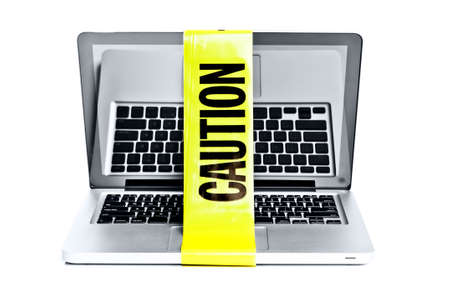 Laptop with caution tape around it  Stock Photo - 13430138