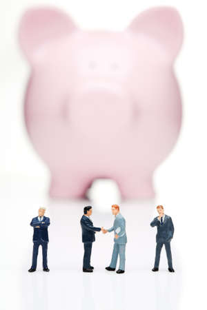 Piggy bank with business figures shaking hands