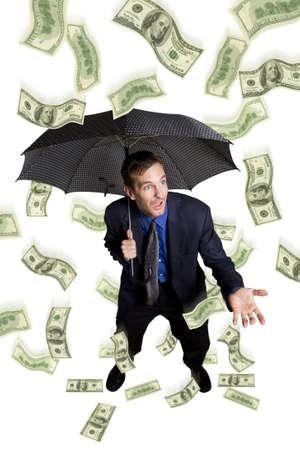 Raining money on a businessman with umbrella