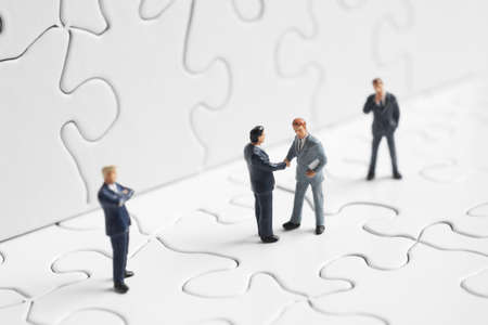 conundrum: Business figures shaking hands on a puzzle  Stock Photo