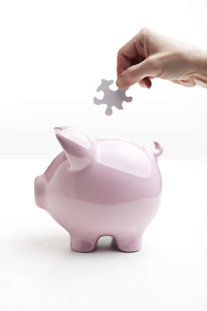 conundrum: Hand dropping a puzzle piece into piggy bank