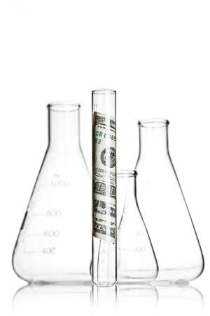 Test tube with 100 dollar bills in front of flasks