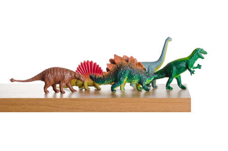 out dated: Dinosaurs figurines placed together on a ledge Stock Photo