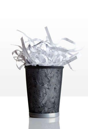 Trashcan full of shredded paper on a white tabletop photo