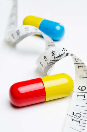 Giant pills placed with a tape measure