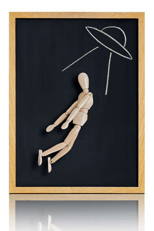 abduct: Manikin, anatomical model, placed on a chalkboard with an alien spaceship drawn on it