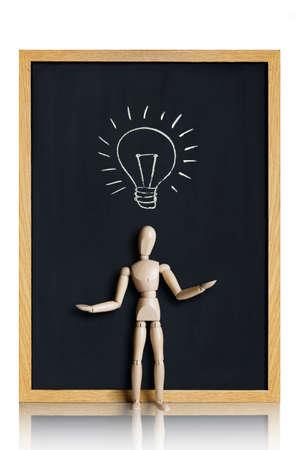 Manikin, anatomical model, placed on a chalkboard with a lightbulb drawn on it  版權商用圖片