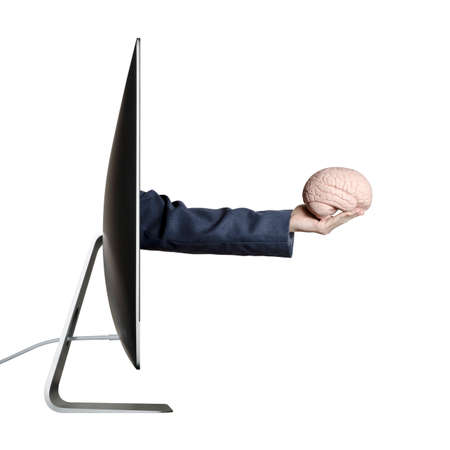 Hand holding a human brain extending out from a computer screen