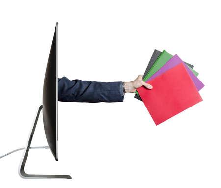 Working online  Hand holding folders, extending out from a computer screen  Stok Fotoğraf