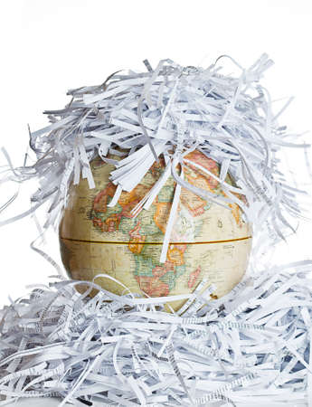 trashed: Earth globe covered with shredded paper Stock Photo