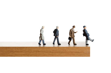 Business figurines walking off a ledge Foto de archivo