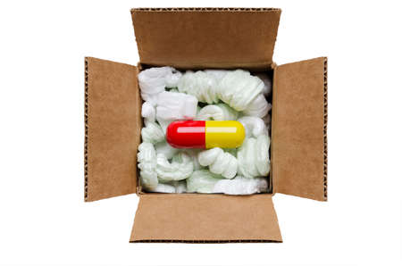 Large pill in a box with packaging peanuts
