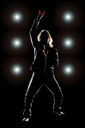 Man with long hair holding a microphone, against a black background with lights behind him