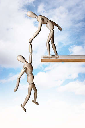 brink: A manikin holding another manikin from falling off a ledge Stock Photo