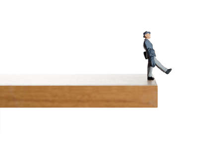 Business figurine walking off a ledge Imagens - 25406715