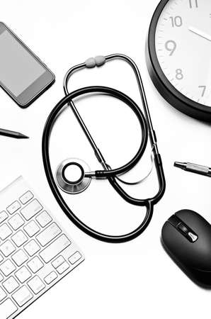 Stethoscope, pen, computer mouse, clock, and cellular phone  photo