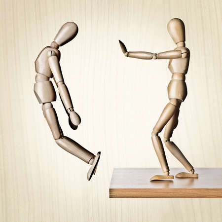 are thrust: Two manikins, one pushing the other off an edge