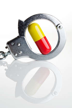 illicit: Pills and handcuffs together on a white tabletop