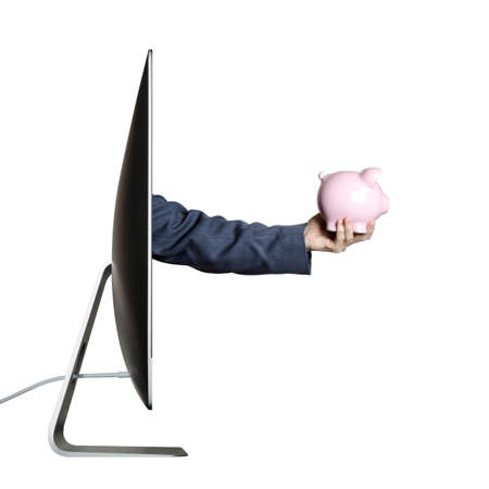 Hand holding a piggy bank, extending out from a computer screen