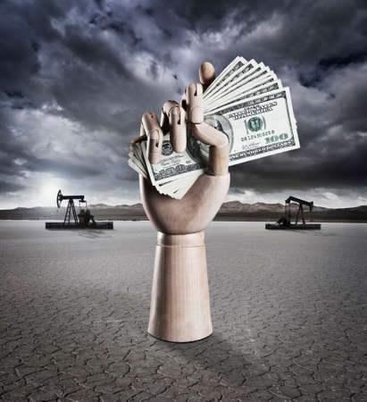 Manikin hand holding money in dry lake bed with storm clouds and drilling rigs in background Banco de Imagens