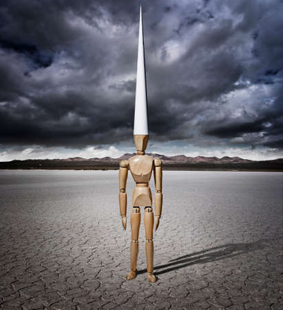 Artist manikin with Dunce cap in a dry lake bed with storm clouds