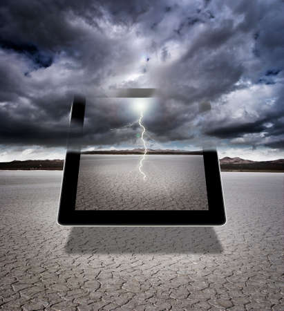 Composite of a digital tablet with storm clouds and lightning in a dry lakebed