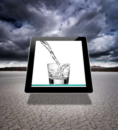 A digital tablet in a dry lake bed with an image of a glass of water being poured