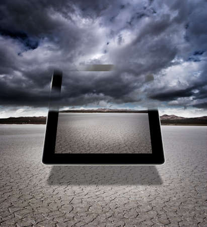 Composite of a digital tablet with storm clouds in a dry lakebed Banco de Imagens