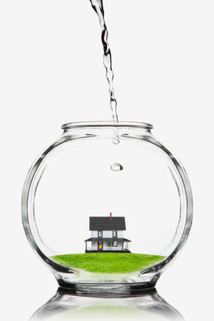 Water pouring on a house in a fishbowl  Banco de Imagens