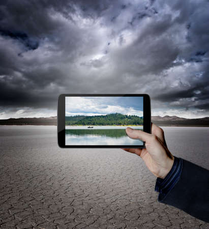 Hand holding a digital tablet in a desert with a lake on the screen