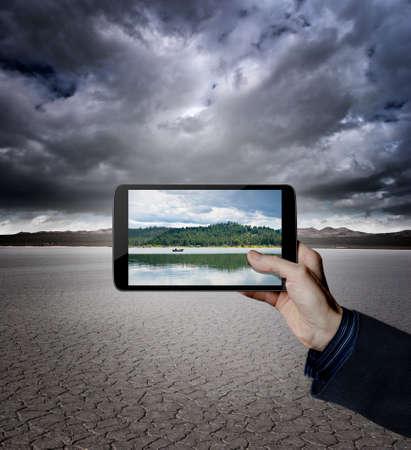 conservacion del agua: Mano que sostiene una tableta digital en un desierto con un lago en la pantalla