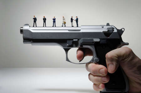 Gun lobby, business figurines on a handgun