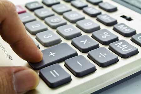 adding: Business growing, a finger press on the adding button on calculator Stock Photo