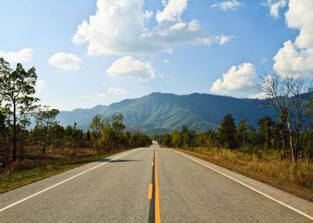 Straight country road to the mountain in Thailand