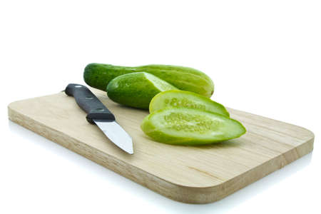 trencher: Cucumber sliced with kinfe on chopping board Stock Photo