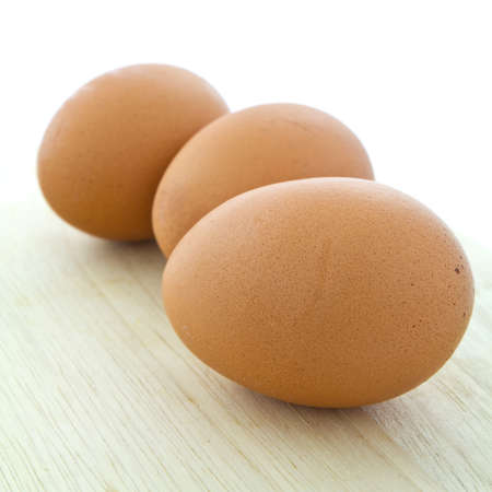 まな板: 木製のまな板に卵 3 個