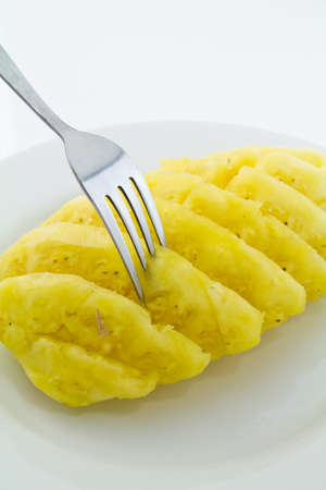 Pineapple on white dish with fork photo