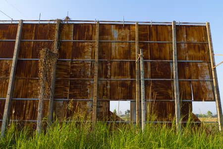 Huge rusty billboard in grass field photo