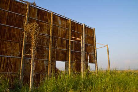 Huge rusty billboard in paddy and grass field photo