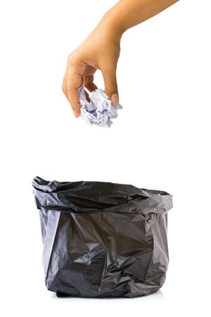 black plastic garbage bag: Hand going to drop garbage paper into the bag