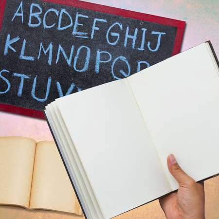 Hand holding the opened notebook with blackboard and book background photo